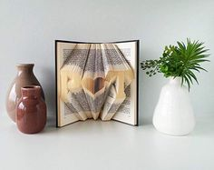 Folded Book Art Anniversary gift Two initials with a heart. Folded Book Art is a very unique and special gift to give for an Anniversary or Wedding. This book displays two initials separated by a heart. Any two initials can be folded. 9th Wedding Anniversary, Cotton Anniversary Gifts, Anniversary Gifts For Parents, Folded Book Art, Personalized Wedding Gifts, Initials, Heart, Book Displays, Custom Book
