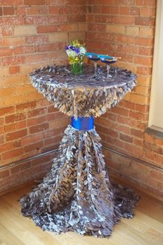 Silver cocktail table with dark blue ribbon detail.