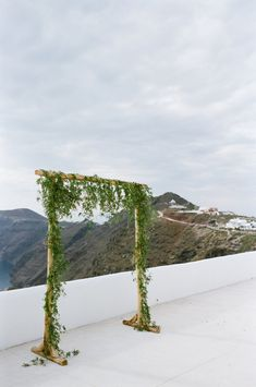 simple greenery covered ceremony arch | Photography: Les Anagnou