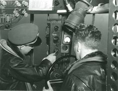 Two U.S. Navy Airship Squadron 24 crew members steering their K-28 airship, written below the image, 'Resume Course'; from the booklet, 'An Operational Flight ZP-24'...Credit: unknown (Smithsonian Institution)