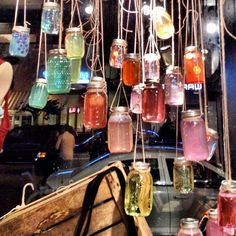 Glass jars are repurposed in this colourful hanging window display. This would be great and cheap as a hanging display at a wedding with the water colored in your wedding colors.