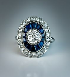 An Art Deco Diamond and Sapphire Engagement Ring, French, circa 1925. A vintage 18K white gold milgrain ring of an oval shape centered with a prong-set sparkling old European cut diamond outlined by a row of tapered calibre cut deep blue sapphires and further set with a border of old single cut diamonds.