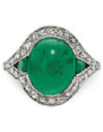 An Art Deco emerald and diamond ring, circa 1925. Set with an oval cabochon emerald, flanked on either side by a calibré-cut emerald, to the old-cut diamond surround, mounted in platinum. #ArtDeco #ring