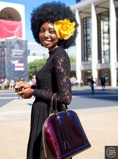 Big hair + flower hair accessory + lace dress + patent leather bag
