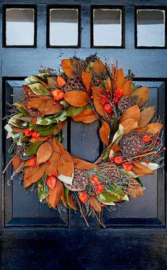 Show off the textural beauty of dried lotus pods with a framework of lush greenery. We love the look this elegant fall wreath! #falldecor #fallideas #wreathideas #fallwreath #wreath #bhg