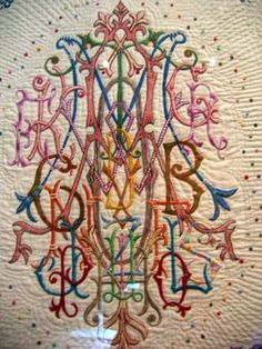 A Most Elaborate Monogram. The source says it's a quilt, so probably appliqué and embroidery combined. WOW! Love it!