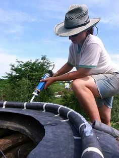 Installing the homemade skylight on a frame made from a tractor tire.