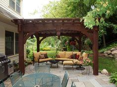 pergola en bois massive qui abrite des canapés et une petite table ronde, pergola qui est un véritable bijou