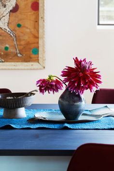 Showy dahlias burst forth from handmade ceramics on the serene dining room tablescape.
