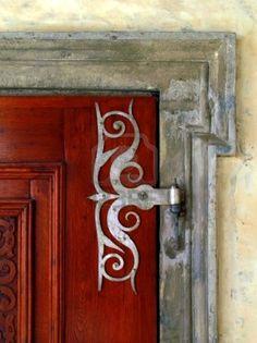 Ornamental door hinge on red door ...