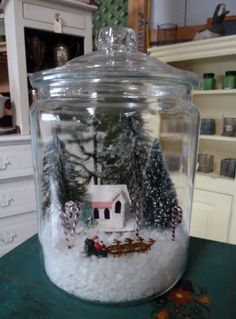 I started out with some plain old rock salt in the bottom of the jar  and added a few bottle brush trees, some small shiny candy canes, a vintage cardboard house ornament and a  Santa & Sleigh from a Christmas Village Set I have.  You can literally use anything you have We all probably have way too much Christmas decor  packed away....cause it is so irresistible    Here is the finished product.