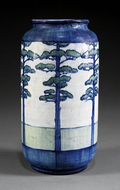 Newcomb College Art Pottery Vase   1902 Decorated by Desiree Roman with a repeating pattern of tall Pine trees   Newcomb cipher, decorator's mark, Joseph Meyer's potter's mark, reg. no. P43, and U for buff clay body, height 9 1/2 in