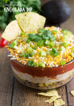 Spicy Enchilada Dip - A spicy and packed enchilada dip that is vegetarian. Packed with black beans, refried beans, corn, salsa, enchilada sauce, and an array of various toppings.