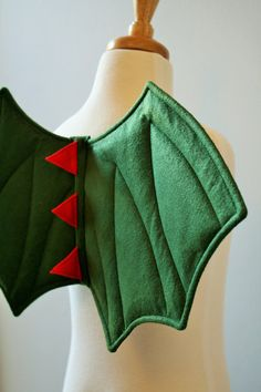 Childrens dragon (or dinosaur) wings for every day dressing up play - or to finish an amazing fancy dress costume! A huge favourite with all boys and girls, Im delighted to bring these back to Etsy this year.  Layers of green felt and wadding, with a centre band of 3 red felt scales and elastic arm loops. These are strong and sturdy, whilst being padded and fully NON-WIRED. Perfect for childsplay; retaining shape whilst being safe enough to roll about it. No metal, no wire, no glue. Every…