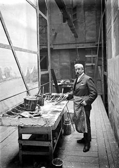 A well-dressed man wearing a dirty apron and holding a paintbrush, on the scene-painting gallery floor at the Theatre Royal, Birmingham. Large hand-painted 'flats', the backdrop scenes for the theatre stage, can be seen to left and right.