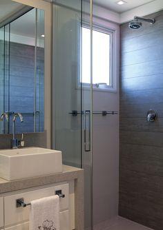 Mantendo a mesma proposta cromática, o banheiro ganhou revestimento em porcelanato de padrão amadeirado na parede da área do box.