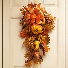 The colorful creation of this unique Pumpkin and Gourd Door Swag offers a different type of decoration for the Fall Season. Pumpkins, gourds and grape leaves are nestled in a bed of warm colored yellow and orange leaves, topped with a beautiful orange bow. Add a touch of elegance and warmth to your home, or any other place you chose to put it.