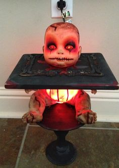 Creepy baby doll, painted and put lights in body. Project cost was $3.25.