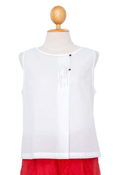 This light and airy sleeveless top with its short, flared form is made from gorgeous 100% cotton for coolness and comfort in the hot summer sun.  To make it extra special, the gentle round neck meets at a single front pleat, hand-embroidered and finished with two tiny buttons that transform this simple summer tank into something for work.