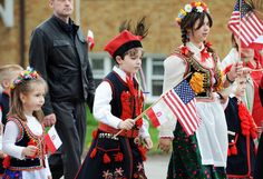 Children dressed in traditional Polish clothing waved American and Polish flags during the Polish Constitution Day parade in Parma.