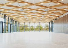 A latticed canopy overhangs the zigzagging glass facade of this riverside community hall.