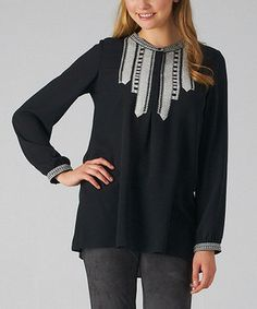 This bib-style blouse with barrel sleeves provides a modest and stylish look with its embroidered appliqué. An inverted pleat creates a flowing silhouette with soft, lightweight fabric.