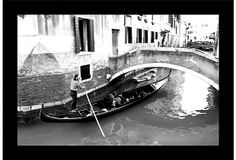 A gondola for two passes under a bridge in Venice on this giclée print.