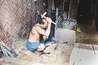 Bangladeshi man hammering a metal piece in a blacksmith workshop in Rangamati, Chittagong Division, Bangladesh, Asia