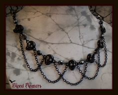 This was the inspiration for a red and black necklace.  In place of the skulls I used black Rondelles, for the silver-red glass pearls, and clear 2mm crystals in between the pearls.  Instead of pins, I strung the beads.