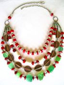 This is a four-strand piece made up of coral, green glass, heishi, and seed beads. A study in high contrasts and a mixture of metallic tones. An adjustable sterling silver chain and clasp bring it all together.