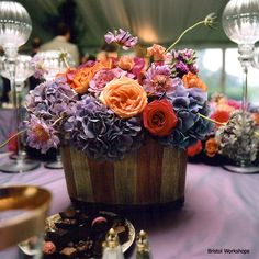 rustic wedding centerpiece with purples, orange, pink, and reds