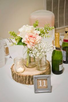 Short tables with mason jars, cream and blush floral with babies breath. Tea…
