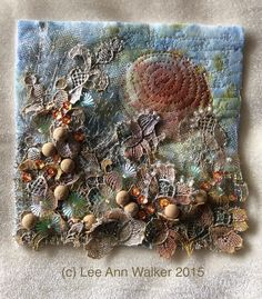 "Lee Ann Walker, 47-2"" Frosted Morning 12/8/2015. 6"" square. Machine embroidered painted baby wipe (thanks Nan Jacobson!), painted antique lace and buttons, beads and sequins."