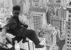 A worker pauses for a sandwich, resting on a girder during the construction of a skycraper, 1930