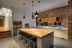 Love the blackbutt timber bench top, love the concrete floors, love the clever cabinetry, only thing I don't love is the cabinets over the mirror splashback.