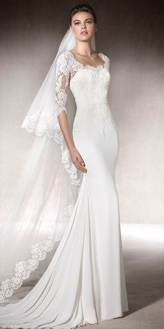 Sophisticated mermaid dress in gauze and tulle, with lace appliqués on the bodice, a round-neckline and 3/4 sleeves.