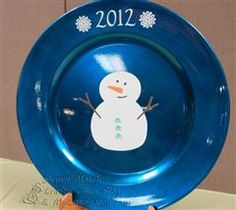 For this project I purchased a plate for $1 at a craft store and used Square 1 adhesive backed material (which is a great substitute for vinyl) to decorate the plate.  The snowman is from the Doodlecharm Cricut cartridge.  I used Viva Decor for the eyes and the mouth and then glued some buttons on to the front of the snowman.