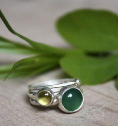 """""""Thé vert d'Himalaya"""" est une combinaison de trois bagues en argent et de cabochons. La première bague comporte une agate vert émeraude faisant référence aux feuilles de thé plus foncées et la seconde un péridot pour les jeunes pousses. Une petite touche de fraicheur enveloppe ces deux pierres semi-précieuses.  La troisième bague est faite d'un anneau martelé surmonté d'une petite boule en argent"""
