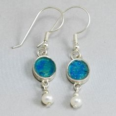 The amazing rich blues of Roman glass in a round sterling silver setting with sterling bead and freshwater pearl suspended below. Handmade in Israel