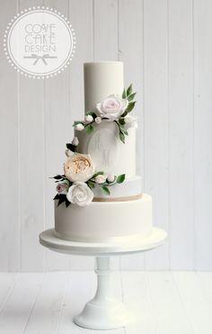 Contemporary wedding cake with custom monogram and sugar flower wreath
