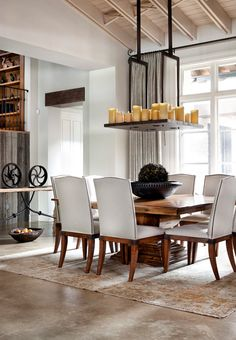 White and natural dining room with concrete floor, rustic table and console