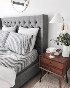 dream bedroom set of a gray tufted upholstered headboard and side panels, striped sheet set with white duvet and euro pillows. midcentury modern wood side table and wall sconces above for reading lights #PillowSet