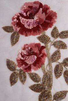 Hand-made motif of a sequined rose with brilliantly iridiscent leaves