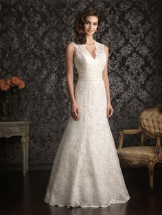 9013 - A sophisticated design with beautiful details. This slim line gown features delicate lace throughout. The bodice has a dramatic v-shaped neckline and beautiful key-hole back while a chapel length train finishes the dress perfectly.