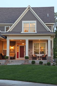 """Traditional exterior by Ridge Creek Custom Homes!!! Bebe'!!! Great front porch and attractive entry with colorful rusty red front door!!"""" Simple pair of garden chairs and simple boxwood foundation plantings add attractive touches to the porch and entryway!!!"""