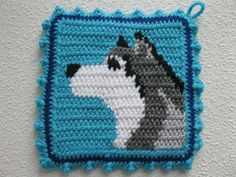 Alaskan malamute pot holders. Handmade, turquoise blue potholders featuring husky dogs. This is an original crochet design. The malamutes are crocheted in white, silver, grey, and black against a turquoise blue background. The dogs have chocolate brown eyes with black centers and a black nose. The pot holders are double thick and the back panel is loom knit (double thick) with turquoise blue. Pot holders are bordered with dark blue and finished with a turquoise blue crochet ruffle.  This pot…