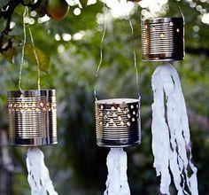 Stanzen Sie leere Blechkonserven Löcher, kleben unten Krepppapierbänder an, hängen die Dosen mit einem Draht auf und stellen ein Teelicht hinein - fertig!