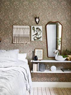 Sängen är bäddad med påslakan från Ikea och på väggen sitter en bonad, horn och spegel, alla vintage. Fågelprintet kommer från Balders Hage och på hyllan skymtar en tavla med teckenspråk från Vanilla Fly. Svanen är ett loppisfynd och glasvaserna är köpta på Åhléns.