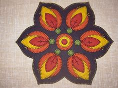 "Penny Rug Fireside Tablemat pattern #tm-03 size - 17 1/2"" diameter. Based on the beautiful Pennsylvania Dutch folk art from Lancaster County, this tablemat brings to mind warm Autumn evenings by the fireside."