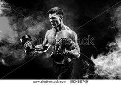 Handsome bodybuilder doing exercise with dumbbell. Studio shot. Black and white photo. Smoke